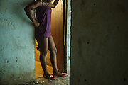 "Nicole, 16, stands in the doorway of one of the rooms where she meets clients in a brothel in Abidjan, Cote d'Ivoire on Wednesday July 17, 2013. Nicole started working as a sex worker after running away from home, where her mother used to beat her. She says she can have up to 10 or 20 clients in a day; each of them pays 1000 CFA (2$). ""When I started I went for a whole week without using condoms. I was new, I didn't know"", she says. ""Sometimes the police come to catch us. We have to pay them 3000, 5000 or 10,000 so that they leave us alone. Other times you have to sleep with them."" Nicole went to school up to grade 5."