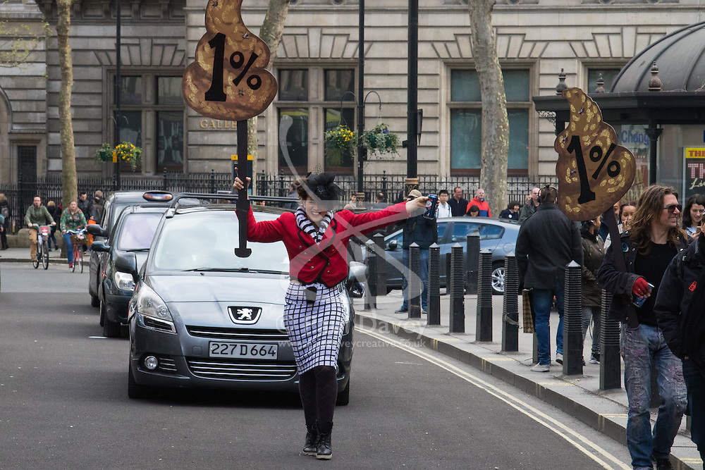 """London, April 16th 2016. A woman carrying a poo-shaped """"1%"""" placard marches in front of traffic as thousands of people supported by trade unions and other rights organisations demonstrate against the policies of the Tory government, including austerity and perceived favouring of """"the rich"""" over """"the poor""""."""