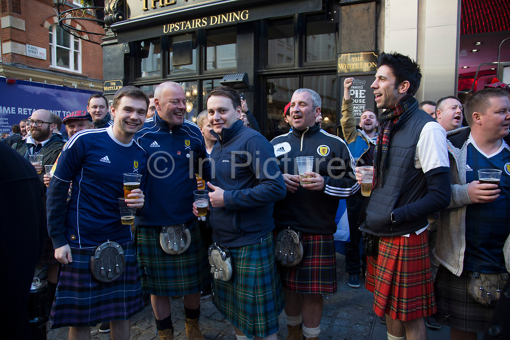 Scotland fans wearing kilts in joyous mood drinking and singing together in Covent Garden ahead of their football match, England vs Scotland, World Cup Qualifiers Group stage on 11th November 2016 in London, United Kingdom. The Home International rivalry between their respective national teams is the oldest international fixture in the world, first played in 1872.