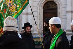 London, February 8th 2015. Muslims demonstrate outside Downing Street  to denounce the uncivilised expressionists reprinting of the cartoon image of the Holy Prophet Muhammad. PICTURED: A lone Jew passes the protest.