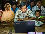 07 NOVEMBER 2014 - SITTWE, RAKHINE, MYANMAR: Rohingya Muslims in an IDP camp near Sittwe use Skype and internet telephony to talk to relatives in Malaysia. After sectarian violence devastated Rohingya communities and left hundreds of Rohingya dead in 2012, the government of Myanmar forced more than 140,000 Rohingya Muslims who used to live in and around Sittwe, Myanmar, into squalid Internal Displaced Persons camps. The government says the Rohingya are not Burmese citizens, that they are illegal immigrants from Bangladesh. The Bangladesh government says the Rohingya are Burmese and the Rohingya insist that they have lived in Burma for generations. The camps are about 20 minutes from Sittwe but the Rohingya who live in the camps are not allowed to leave without government permission. They are not allowed to work outside the camps, they are not allowed to go to Sittwe to use the hospital, go to school or do business. The camps have no electricity. Water is delivered through community wells. There are small schools funded by NOGs in the camps and a few private clinics but medical care is costly and not reliable.   PHOTO BY JACK KURTZ