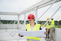 Female architect with blueprint at construction site, Munich, Bavaria, Germany, Europe