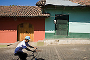 11 JANUARY 2007 - LEON, NICARAGUA:  A man rides his bicycle past colorful homes in Leon, Nicaragua. Leon was widely damaged in the 1972 earthquake and Nicaraguan revolution in 1979, many buildings are still pockmarked from bullet holes left from the war. But the city is experiencing a bit of a revival because of the proximity of the beaches of Poneloya, Las Senitas Nicaragua, about 10 miles from Leon. Nicaragua's Pacific beaches are relatively undiscovered. Small hotels and rental homes are starting to be developed but there is nothing like the rampant commercial development of Mexico's Pacific beaches.  PHOTO BY JACK KURTZ