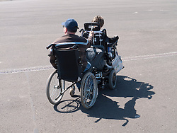 Wheelchair user towing another wheelchair user...