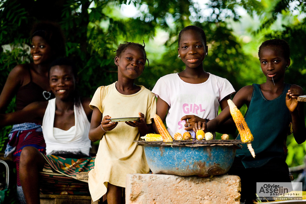 Girls roasting corn by the roadside in Dimbokro, Cote d'Ivoire on Friday June 19, 2009.