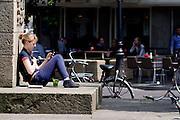 Op het Janskerkhof in Utrecht geniet een meisje met een kopje muntthee van de eerste zomerse dag in 2013, terwijl ze met haar mobiele telefoon bezig is.<br /> <br /> At the Janskerkhof in Utrecht a girl is enjoying the first summer day of 2013 with a cup of mint tea, while she is busy with her mobile phone.