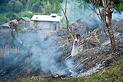 A young girl chops down charred stumps in a recently burned field with a long steel knife called a dao, the same kind of knife the headhunters used to use to chop off enemy heads.