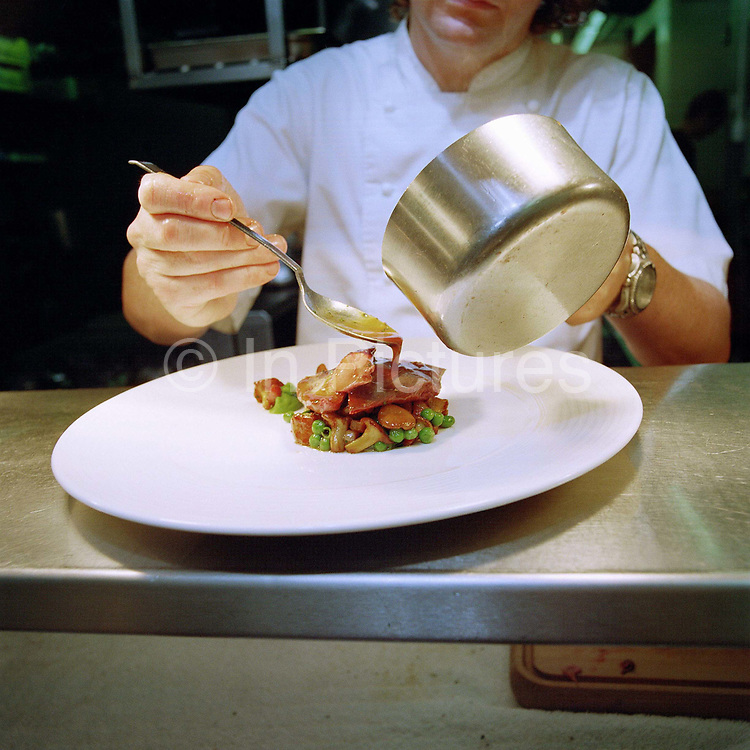A chef prepares a dish for the table in the kitchen of The Kitchin restaurant, Leith, Edinburgh. Tom and Michaela Kitchin opened their restaurant, The Kitchin on Edinburgh's Leith waterfront in 2006. The Kitchin presents modern British seasonal cuisine influenced by French cooking techniques and an appreciation of the best quality ingredients available from Scotland's natural larder.