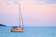 A sailing boat moored in the bay with two people on the deck off Korcula at sunset. Prizba village. Korcula Island. Prizba, Riva Apartments, Danny Franulovic. Korcula Island. Dalmatian Coast, Croatia, Europe.