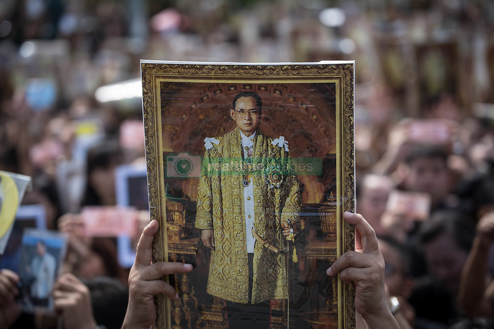 October 22, 2016 - Bangkok, Bangkok, Thailand - Mourners dressed in black gathers around the Grand Palace while carrying several portraits of the king as they wait to perform the Royal Anthem at Sanam Luang in Bangkok, Thailand on October 22, 2016. More than 100.000 mourners from across Thailand came during the long week end holiday to sing the Thai Royal Anthem to pay respect to the late Thailand King Bhumibol Adulyadej who passed away on October 13, 2016 at Siriraj Hospital. Thai King Bhumibol Adulyadej was the world's longest reigning monarch and died at the age of 88 after a long illness since several years, he was the most unifying symbol for Thai people and leaving behind him a divided country under military control. (Credit Image: © Guillaume Payen/NurPhoto via ZUMA Press)