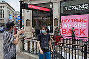"In the 24hrs that a further 38 died from Coronavirus, bringing the total to 41,736, a further easing of the UK's Covid pandemic lockdown restrictions took place with many high street shops today being allowed to re-open after three months of forced closure. Prime Minister Boris Johnson, wanting to stimulate the economy, has urged people to ""shop with confidence"" and long queues formed outside the main brands. But unlike on public transport, face coverings are not compulsory so shop floors and shopping practices have had to be adapted to ensure customers' social distances, amid fears of a second infection wave. Shoppers queue outside a shop and others walk past a blocked-off entrance steps at Oxford Circus underground station, on 15th June 2020, in London, England."