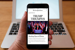 Detail of iPhone smart phone showing online mobile  newspaper front-page headline from The New York Times  following Donald Trump's victory in 2016 US Presidential Election