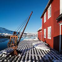 Snow covered deck outside red Rorbu building, Steine, Vestvågøy, Lofoten Islands, Norway