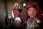 Guests and mother watching the veil celebration: before moving to her new husband's camp, Ikhbal, a recently married Kyrgyz girl, will exchange the red veil of the unmarried girl for the white veil signifying that she is now a married woman...The Kyrgyz settlement of Ech Keli, above Chaqmaqtin lake, Er Ali Boi's camp...Trekking through the high altitude plateau of the Little Pamir mountains, where the Afghan Kyrgyz community live all year, on the borders of China, Tajikistan and Pakistan.
