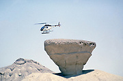 Bell 206 JetRanger helicopter taking off from rock outcrop Arabian desert, Saudi Arabia oil industry 1979