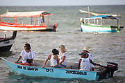 Boats in the sea, fishermen taking people out to make offerings to Yemanja. February 2nd is the feast of Yemanja, a Candomble Umbanda religious celebration, where thousands of adherants visit the Rio Vermehlo Red River to make offerings of flowers and prayers, paying their respects to Yemanja, the Orixa goddess of the Sea and water.