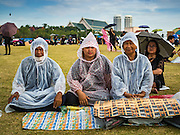 22 OCTOBER 2016 - BANGKOK, THAILAND:  Mourners sit in the rain on Sanam Luang in Bangkok. Sanam Luang, the Royal Ceremonial Ground, was packed Saturday with more than 100,000 people mourning the Monarch's death. The King died Oct. 13, 2016. He was 88. His death came after a period of failing health. Bhumibol Adulyadej was born in Cambridge, MA, on 5 December 1927. He was the ninth monarch of Thailand from the Chakri Dynasty and is also known as Rama IX. He became King on June 9, 1946 and served as King of Thailand for 70 years, 126 days. He was, at the time of his death, the world's longest-serving head of state and the longest-reigning monarch in Thai history.      PHOTO BY JACK KURTZ