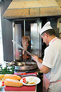 Chef at Ciya Sofrasi Turkish restaurant slicing lamb doner kebab in Kadikoy district Asian side Istanbul, East Turkey