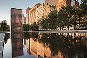 Crown Fountain Video Sculpture with downtown skyline reflected in reflecting pool in Millennium Park Chicago USA