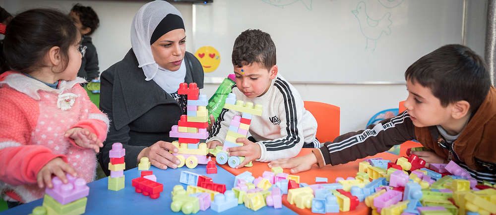 17 February 2020, Zarqa, Jordan: A mother joins to see children play in 'the nanny room' at the Lutheran World Federation community centre in Zarqa. Through a variety of activities, the Lutheran World Federation community centre in Zarqa serves to offer psychosocial support and strengthen social cohesion between Syrian, Iraqi and other refugees in Jordan and their host communities.