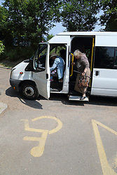 People getting off a minibus next to disabled parking bay.