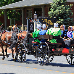 Intercourse, PA - June 12, 2016: An Amish wagon pulled by two horses on a village road in Lancaster County.
