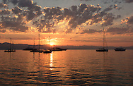 Sunrise behind sailing boats and yachts moored in Gaios harbour, Paxos, The Ionian Islands, The Greek Islands, Greece, Europe