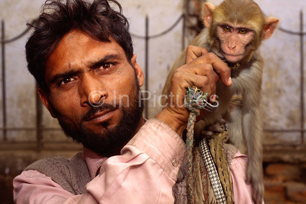 A man and his performing monkey, Shadipur Depot, New Delhi, India<br /> The Kathiputli Colony in the Shadipur Depot slum is home to hundreds of (originally Rajasthani) performers. The artistes who live here - from magicians, acrobats, musicians, dancers and puppeteers are often international renowed by always return to the Shadipur slum.