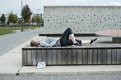 Young woman taking a break after exercising lying on wooden bench and listening to music, Bavaria, Germany