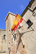 Spanish flag flying Torre de las Ciguenas, in medieval old town, Caceres, Extremadura, Spain