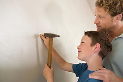 Father son working together hammer wall nail