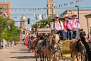 Cowboys riding during the Cheyenne Frontier Days parade past the state capital building July 23, 2015 in Cheyenne, Wyoming. Frontier Days celebrates the cowboy traditions of the west with a rodeo, parade and fair.