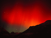 Brilliant red and green aurora over the Mint Glacier Valley, geomagnetic storm during evening of November 5, 2001, Talkeetna Mountains, Alaska.