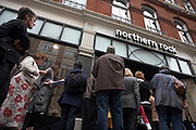 At the height of financial uncertainty, we see from a low pavement angle investors queueing outside the Maddox Street branch of the troubled Northern Rock Bank, off Regent Street, Mayfair, in September 2007. Their hard-earned savings appear to be in jeopardy after the bank announced an emergency loan from the Bank of England. Despite reassurances from officials who insisted that the Bank which has £113bn in assets, was not in danger of going bust, concerned men and women wait in line, some with their faces on view and reading newspapers or more commonly, wishing to remain anonymous and keeping their backs to reporters and cameras. The rush of customers demanding their investments almost spelled the demise of the bank with over £2bn removed from accounts in a few days. Northern Rock struggled since money markets seized up over the summer. .