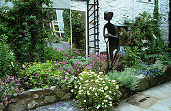 Raised bed with statue of a gardener and mirror framed by trellis.<br /> Please credit sculptor : John Mulvey