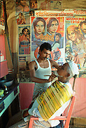 A barber at work shaving a man's beard.  He is wearing a vest (singlet) to keep cool and has 'Bollywood' posters advertising Indian films on display in his barber shop salon in Dacca, Bangladesh. RESERVED USE - NOT FOR DOWNLOAD -  FOR USE CONTACT TIM GRAHAM