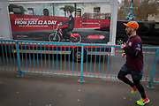 A Santander bike rental vehicle featuring Formula 1 racing driver Jenson Button and a jogger crossing Tower Bridge, on 6th December 2017, in London England.