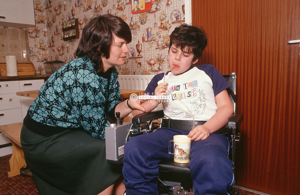 Mother helping young boy with disability; who is wheelchair user; to drink juice through straw,