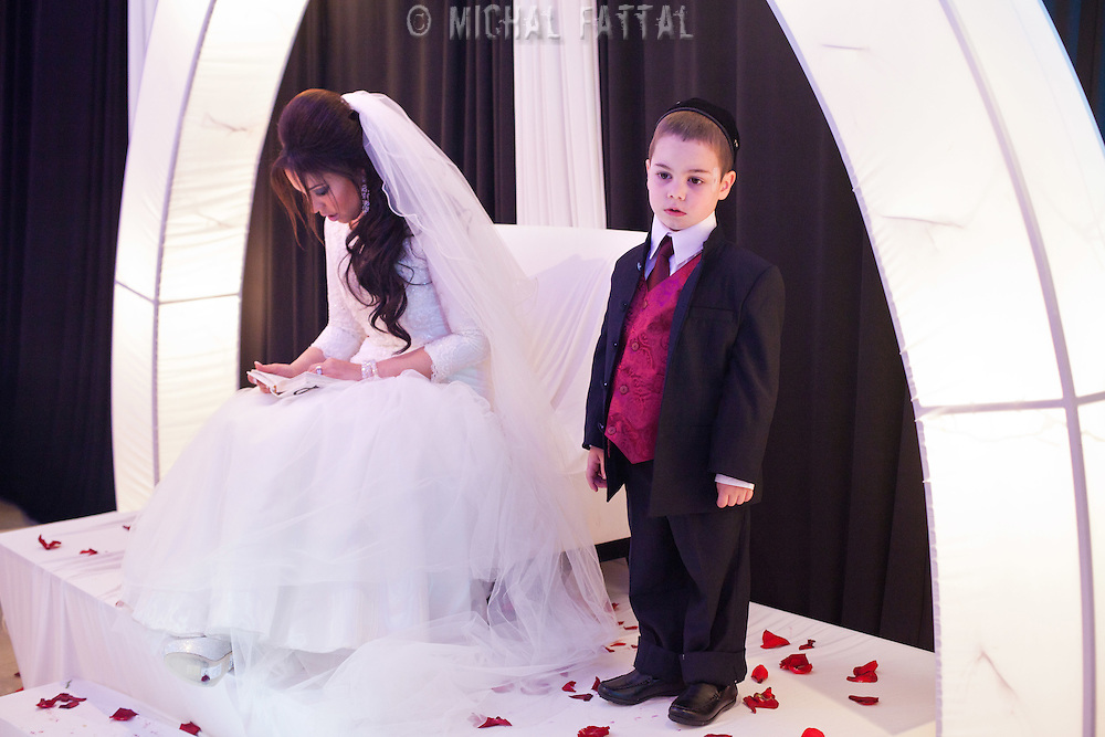 Rahel Berdugo prays a few minutes before the begining of her wedding ceremony in Jerusalem, with her son standing next to her.