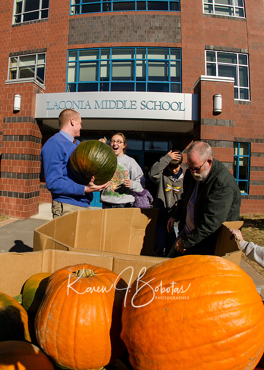 Seth Pingree honors his 7th grade student Nyla Dame's request for a big pumpkin during the unloading process with volunteer Steve Dalzell on Monday morning.  Students will be carving the pumpkins for Saturday's Pumpkin Fest.  (Karen Bobotas/for the Laconia Daily Sun)