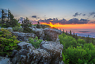 The morning sun rises above the rocky outcrops and an ocean of low lying fog from Bear Rocks Preserve in the Dolly Sods Wilderness of West Virginia.