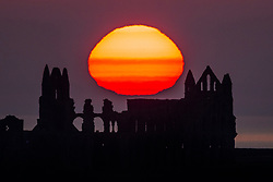 © Licensed to London News Pictures. 20/04/2021. Whitby UK. The sun rises this morning behind the gothic ruins of Whitby Abbey, the inspiration for Bram Stoker's Dracula on the Yorkshire coast. Photo credit: Andrew McCaren/LNP