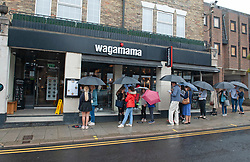©Licensed to London News Pictures 19/08/2020             Sevenoaks, UK. People queuing outside  Wagamama in the rain to make use of the Eat out to help out scheme. Wet weather across large parts of the UK today as shoppers in Sevenoaks High Street, Sevenoaks, Kent get their umbrellas out. The Met office has issued a severe weather warning for 70mph winds over the next two days. Photo credit: Grant Falvey/LNP