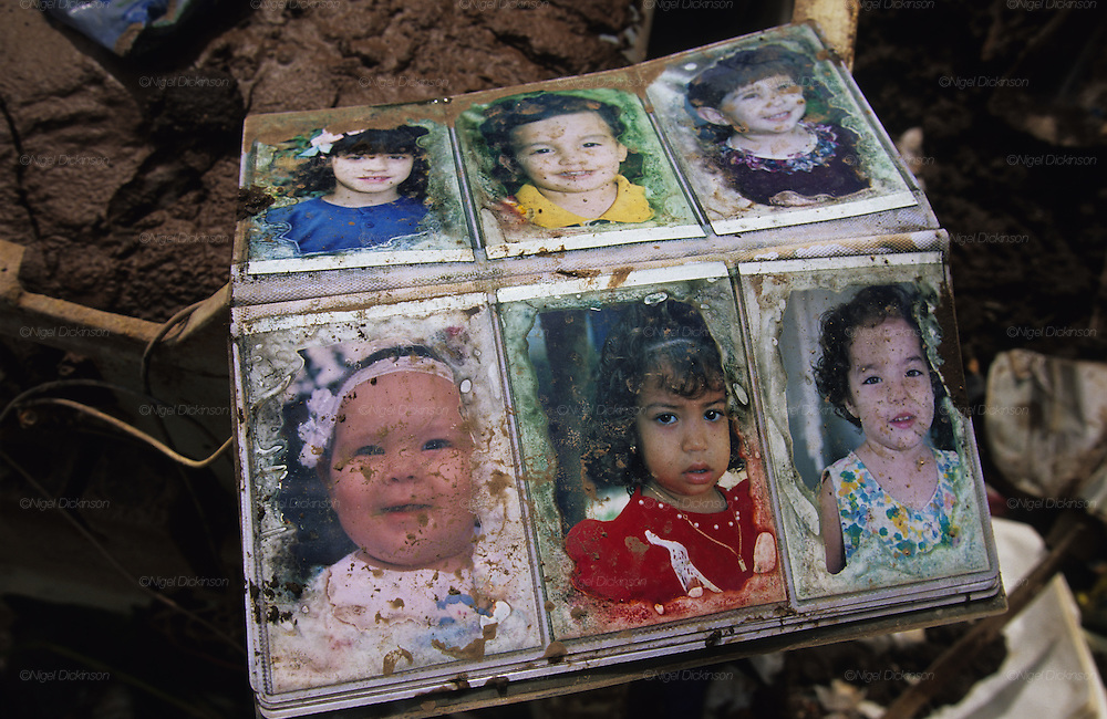Central America, Honduras, Tegucigalpa. Family photo album in ruins. Devastation in the aftermath of Hurricane Mitch. High winds and flooding. Photo albums children. Infrastructure destroyed.