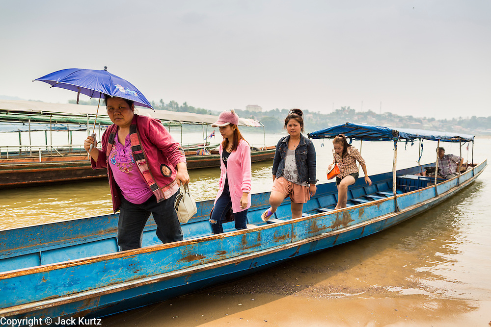 23 APRIL 2014 - CHIANG KHONG, CHIANG RAI, THAILAND: Women get off an informal ferry that takes passengers back and forth across the Mekong River between Chiang Khong, Thailand and Laos. Chiang Rai province in northern Thailand is facing a drought this year. The 2014 drought has been brought on by lower than normal dry season rains. At the same time, closing dams in Yunnan province of China has caused the level of the Mekong River to drop suddenly exposing rocks and sandbars in the normally navigable Mekong River. Changes in the Mekong's levels means commercial shipping can't progress past Chiang Saen. Dozens of ships are tied up in the port area along the city's waterfront.              PHOTO BY JACK KURTZ