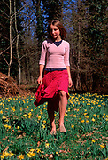 A912P0 Young girl walking in daffodil woods