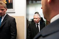 Lapy, woj. podlaskie, 26.10.2010. Spotkanie prezesa<br />  PiS Jaroslawa Kaczynskiego z mieszkancami Lap w ramach kampanii wyborczej do samorzadow. Prezesa PiS ochraniaja byli komandosi pracujacy w firmie ochroniarskiej Grom Group, ktorzy nie odstepuja go na krok. N/z ochroniarze Grom Group czekaja na prezesa PiS pod drzwiami, w glebi Jaroslaw Kaczynski fot Michal Kosc / AGENCJA WSCHOD