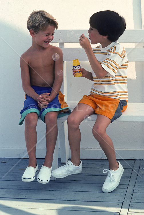 Two boys sitting on a bench playing with bubbles