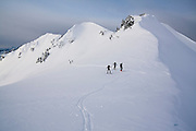 Backcountry skiers tour below Little Diamond Head, Garibaldi Provincial Park, British Columbia, Canada.