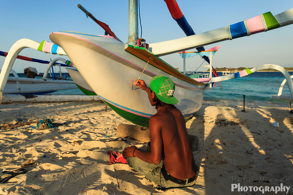 Indonesian boy sitting on the beach painting an outrigger sailboat